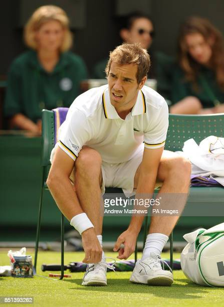 France's Richard Gasquet ties his shoelaces in between games against Spain's Marcel Granollers during day two of the Wimbledon Championships at The...