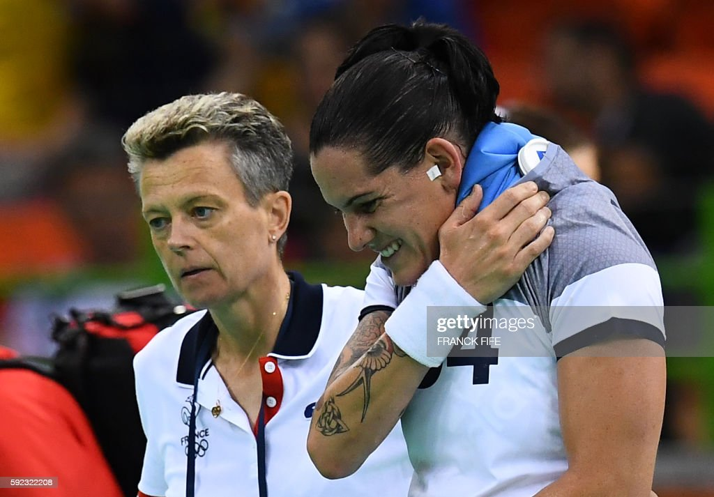 France's right back Alexandra Lacrabere has an ice pack on her shoulder as she leaves the counrt during the women's Gold Medal handball match France...