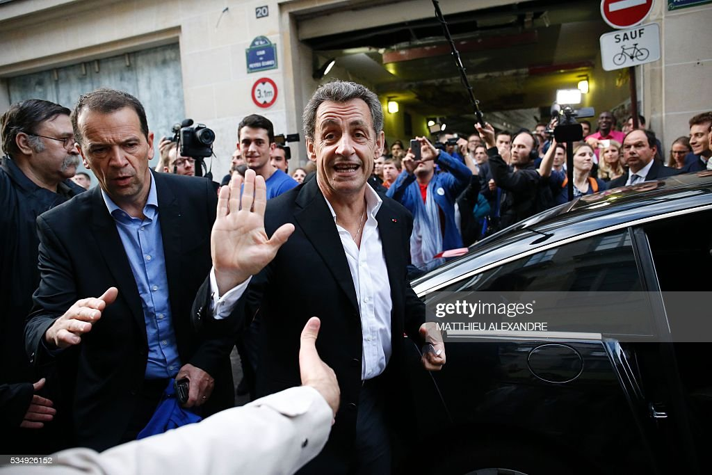 France's right-wing Les Republicains (LR) party president and candidate for the 2017 presidential elections, Nicolas Sarkozy waves as he goes to meet his supporters in a bar of the 10th arrondissement in Paris on May 28, 2016. / AFP / MATTHIEU