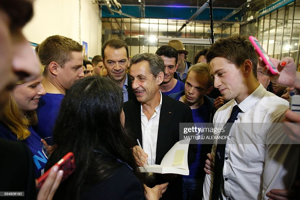 France's right-wing Les Republicains (LR) party president and candidate for the 2017 presidential elections, Nicolas Sarkozy signs his book as he meets his supporters in a bar of the 10th arrondissement in Paris on May 28, 2016. / AFP / MATTHIEU