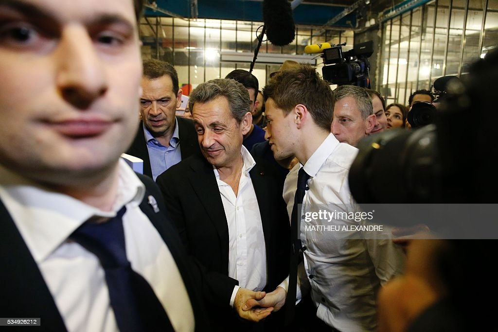 France's right-wing Les Republicains (LR) party president and candidate for the 2017 presidential elections, Nicolas Sarkozy shakes hands as he meets his supporters in a bar of the 10th arrondissement in Paris on May 28, 2016. / AFP / MATTHIEU