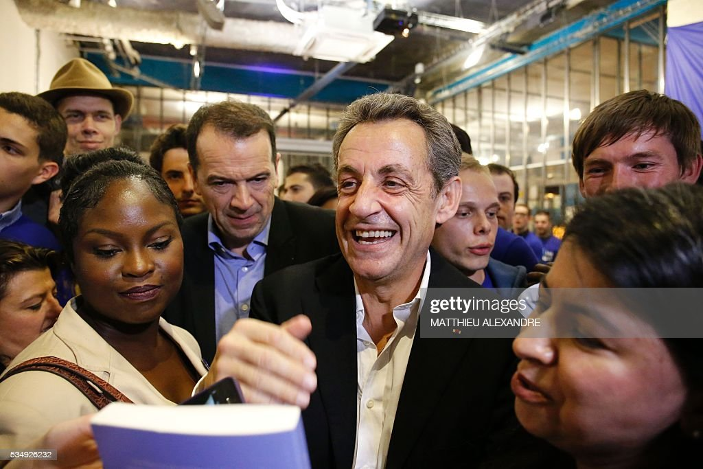 France's right-wing Les Republicains (LR) party president and candidate for the 2017 presidential elections, Nicolas Sarkozy smiles as he meets his supporters in a bar of the 10th arrondissement in Paris on May 28, 2016. / AFP / MATTHIEU
