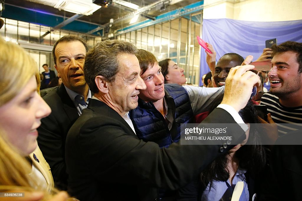 France's right-wing Les Republicains (LR) party president and candidate for the 2017 presidential elections, Nicolas Sarkozy poses for a selfie as he meets his supporters in a bar of the 10th arrondissement in Paris on May 28, 2016. / AFP / MATTHIEU