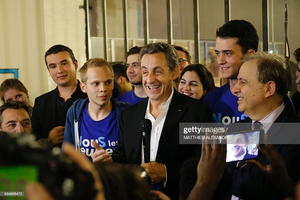 France's right-wing Les Republicains (LR) party president and candidate for the 2017 presidential elections, Nicolas Sarkozy flanked by French Senator Roger Karoutchi, speaks as he meets his supporters in a bar of the 10th arrondissement in Paris on May 28, 2016. / AFP / MATTHIEU