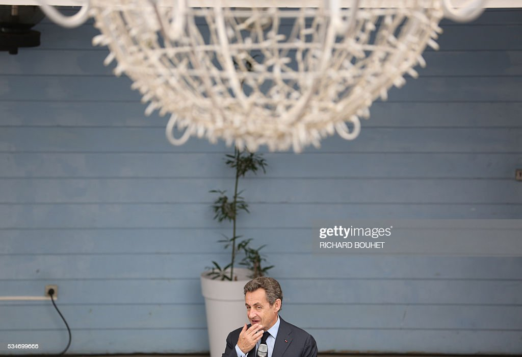 France's right-wing Les Republicains (LR) party president Nicolas Sarkozy (C) is pictured during a welcoming ceremony held ahead of a meeting with local entrepreneurs, on May 27, 2016 in Sainte-Marie, on the French Indian ocean island of La Reunion. / AFP / RICHARD