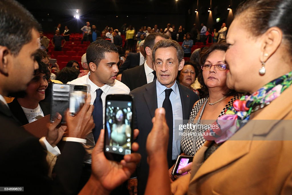 France's right-wing Les Republicains (LR) party president Nicolas Sarkozy (C) poses with militants during a meeting with local heads of the party, on May 27, 2016 in Saint-Paul, on the French Indian ocean island of La Reunion. / AFP / RICHARD