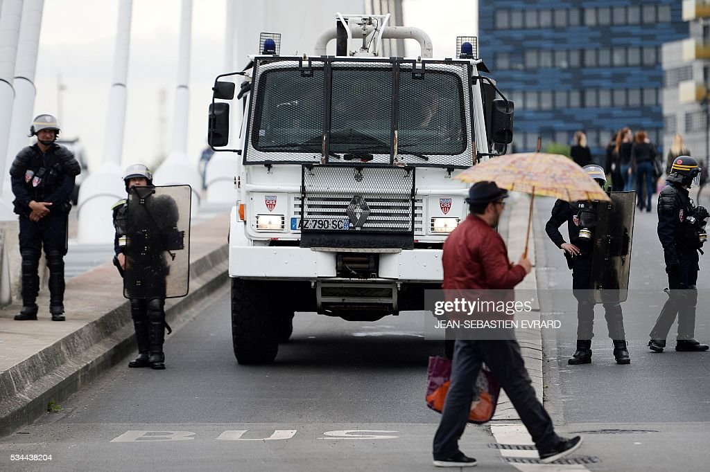 France's riot police stand guard by a water cannon truck as a man crosses the street under an umbrella on May 26, 2016 in Nantes, western France, during an unauthorised demonstration against the government's planned labour law reforms. The French government's labour market proposals, which are designed to make it easier for companies to hire and fire, have sparked a series of nationwide protests and strikes over the past three months. Masked youths clashed with police and striking workers blockaded refineries and nuclear power stations on May 26 as an escalating wave of industrial action against labour reforms rocked France. / AFP / JEAN