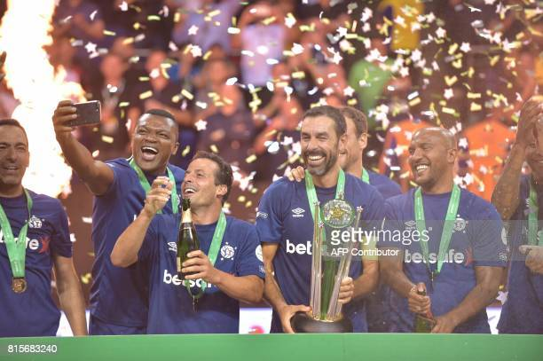 France's Robert Pires holds the trophy as France celebrate their victory after the Star Sixes final football match between France and Denmark at the...