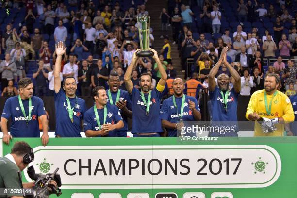 France's Robert Pires holds up the trophy as France celebrate their victory after the Star Sixes final football match between France and Denmark at...