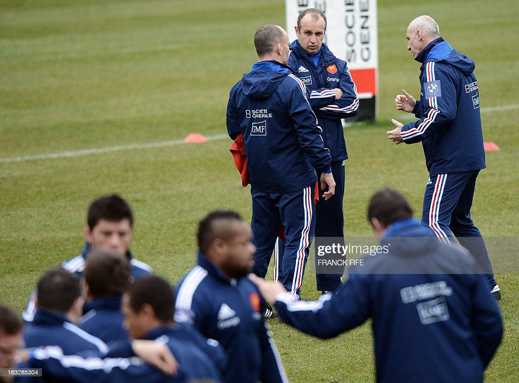 France's rugby union national team assistant coach Yannick Bru, head coach Philippe Saint-Andre and assistant coach Patrice Lagisquet speak together during a training session on March 7, 2013 in Marcoussis, south of Paris, as part of the preparation for the Six Nations rugby union tournament. France will play Ireland in their 2013 Six nations rugby match on March 23, 2013 in Lansdowne Road. AFP PHOTO / FRANCK FIFE