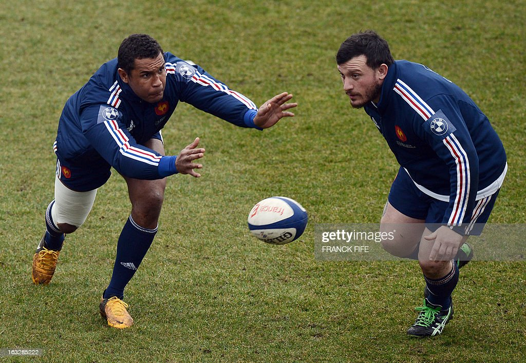 France's rugby union national team captain Thierry Dusautoir (L) passes the ball next to prop Thomas Domingo during a training session on March 7, 2013 in Marcoussis, south of Paris, as part of the preparation for the Six Nations rugby union tournament. France will play Ireland in their 2013 Six nations rugby match on March 23, 2013 in Lansdowne Road. AFP PHOTO / FRANCK FIFE