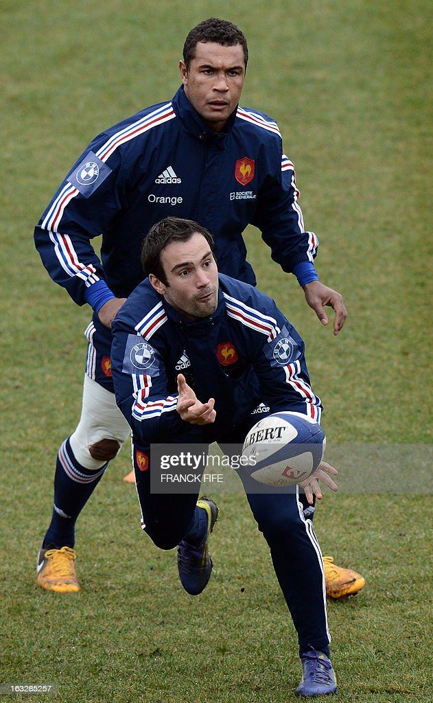 France's rugby union national team scrum half Morgan Parra passes the ball in front of captain Thierry Dusautoir during a training session on March 7, 2013 in Marcoussis, south of Paris, ahead of a 2013 Six Nations tournament match against Ireland on March 23 at Lansdowne Road. AFP PHOTO / FRANCK FIFE