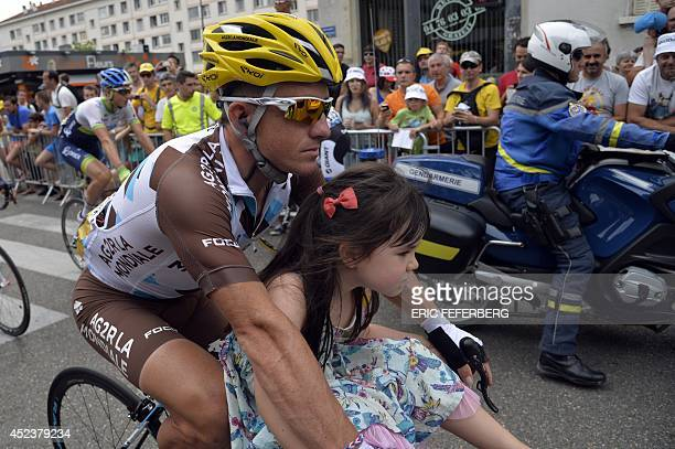 France's Samuel Dumoulin rides with his daugther as he takes the unofficial start of the 177 km fourteenth stage of the 101st edition of the Tour de...
