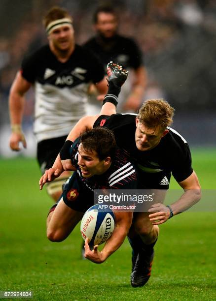 France's scrumhalf Antoine Dupont is tackled by New Zealand's fullback Damian McKenzie during the friendly rugby union international Test match...