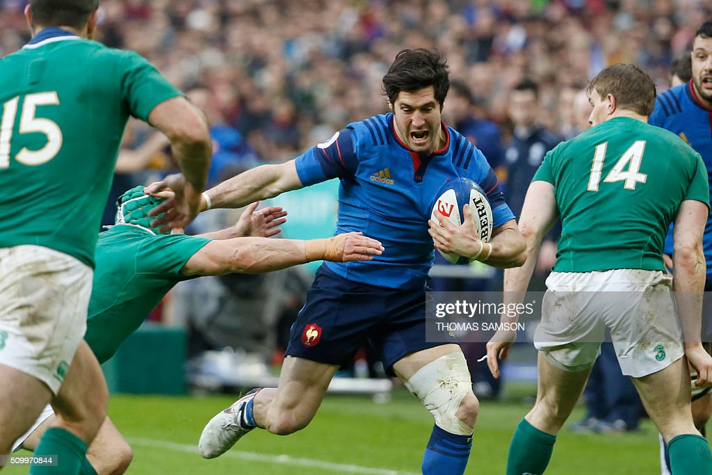 France's scrum-half Maxime Machenaud (C) evades a tackle during the Six Nations international rugby union match between France and Ireland at the Stade de France Stadium in Saint-Denis, north of Paris, on February 13, 2016. AFP PHOTO / THOMAS SAMSON / AFP / THOMAS SAMSON