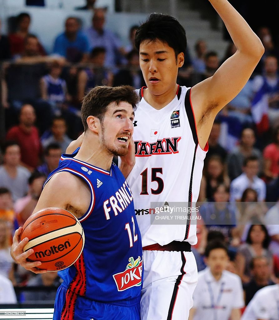 France's shooting guard Nando De Colo (L) vies with Japan's Joji Takeuchi (R) during the basketball match between France and Japan at the Kindarena hall in Rouen on June 28, 2016. / AFP / CHARLY