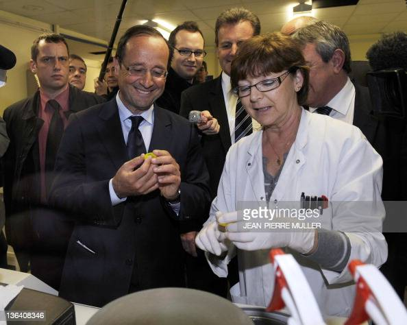 France's Socialist Party candidate for the 2012 French presidential election Francois Hollande listens to a worker as he visits a plant of the Serma...