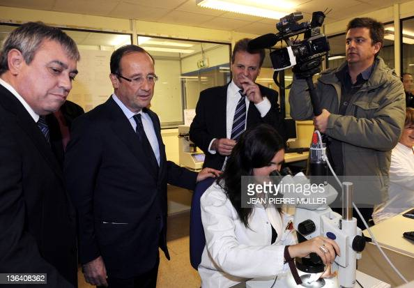 France's Socialist Party candidate for the 2012 French presidential election Francois Hollande looks at a woman working with a microscope as he...