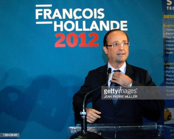France's Socialist Party candidate for the 2012 French presidential election Francois Hollande adjusts his tie before speaking during a visit of a...