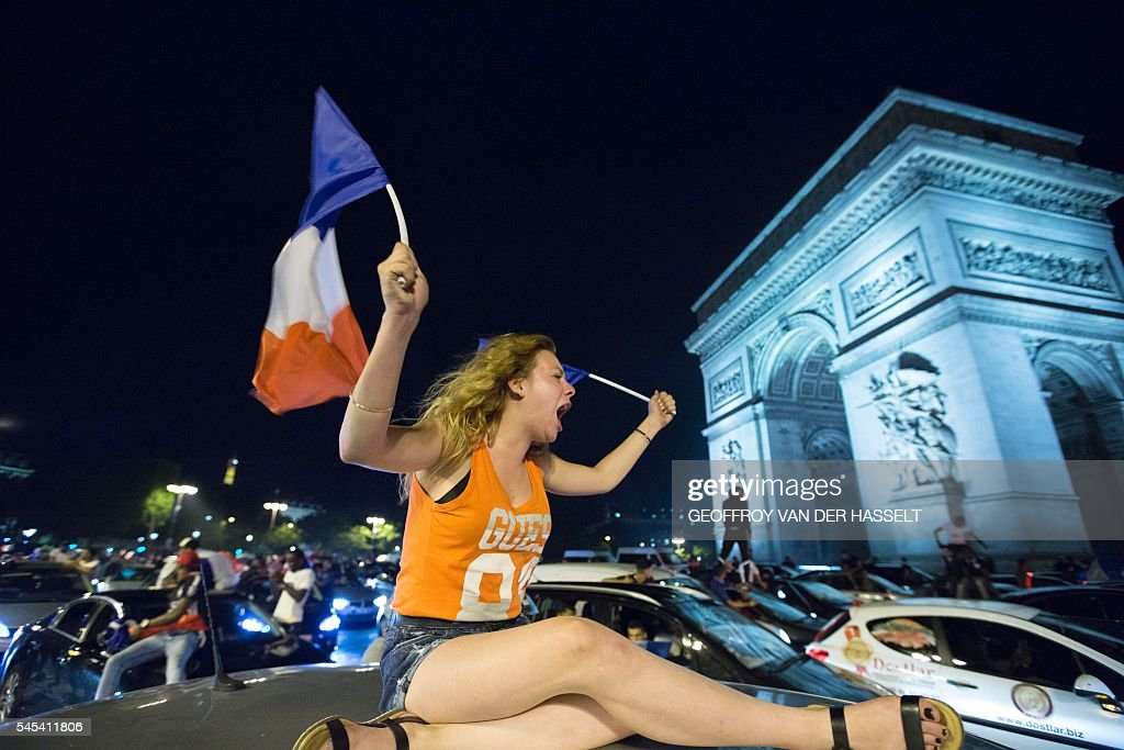 TOPSHOT - France's supporters celebrate after France won the Euro 2016 semi-final football match against Germany, on the Avenue des Champs-Elysees in Paris on July 7, 2016. France will face Portugal in the Euro 2016 finals on July 10, 2016. / AFP / GEOFFROY