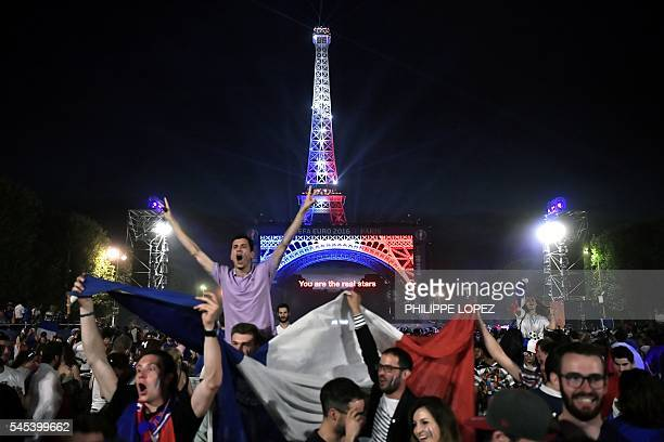 France's supporters celebrate at the Champ de Mars fan zone in Paris on July 7 next to the Eiffel tower illuminated with the colours of France after...