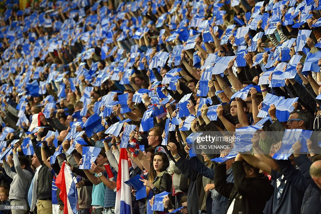 France's supporters hold blue sheets of paper before the friendly football match between France and Cameroon, at the Beaujoire Stadium in Nantes, western France, on May 30, 2016. / AFP / LOIC