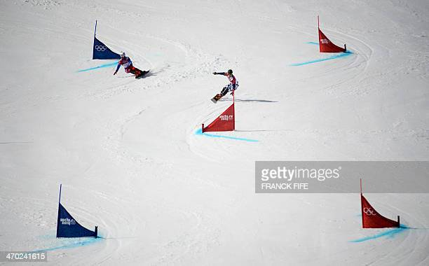 France's Sylvain Dufour and Russia's Vic Wild compete in the Men's Snowboard Parallel Giant Slalom 1/8 Finals at the Rosa Khutor Extreme Park during...