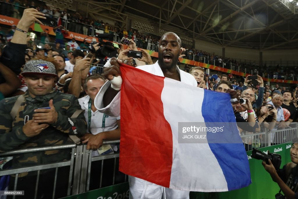 TOPSHOT France's Teddy Riner celebrates with the French flag after defeating Japan's Hisayoshi Harasawa during their men's 100kg judo contest gold...