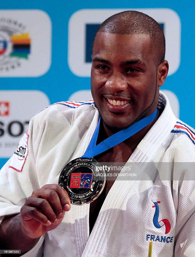 France's Teddy Riner poses on the podium presenting his gold medal after beating South Korea's Kim Sung-Min on February 10, 2013, during the Men +100kg final of the Paris International Judo tournament, part of the Grand Slam, at the Palais Omnisports de Paris-Bercy (POPB) in Paris.