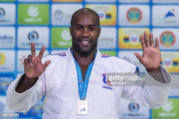 France's Teddy Riner signals eight after becoming World Champion for the eighth time as he poses on the podium during the victory ceremony for the...