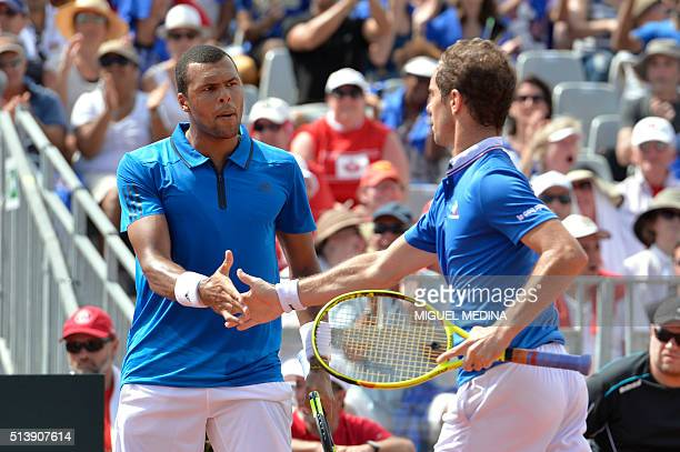 France's tennis player JoWilfried Tsonga shakes hands with teammate Richard Gasquet during the Davis Cup World Group firstround double against Canada...