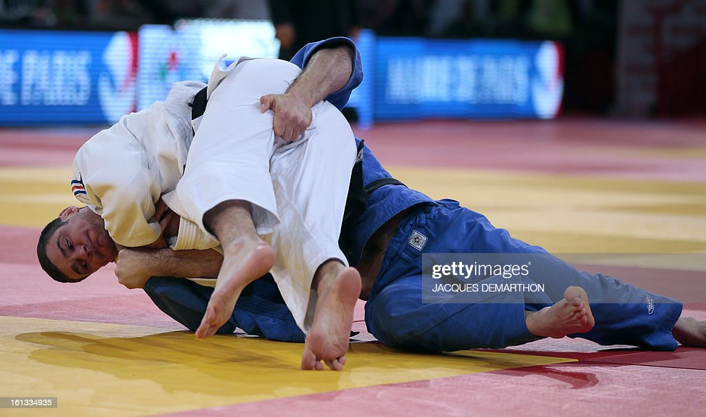 France's Thierry Fabre (white) fights against Georgia's David Loriashvili (blue) on February 10, 2013 in Paris, during the eliminatories of the Men -100kg of the Paris Judo Grand Slam tournament.