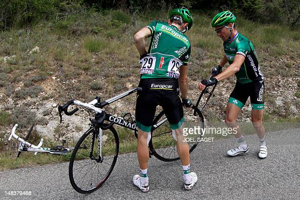 France's Thomas Voeckler helps his teammate compatriot Pierre Rolland to change a wheel in the 191 km and fourteenth stage of the 2012 Tour de France...