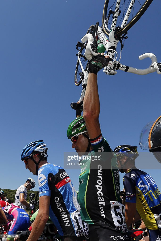 France's Thomas Voeckler (C) raises his bike as riders block the road after falling during the 205.5 km seventh stage of the 100th edition of the Tour de France cycling race on July 5, 2013 between Montpellier and Albi, southwestern France. AFP PHOTO / JOEL SAGET