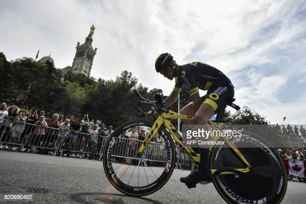 France's Thomas Voeckler rides past the NotreDame de la Garde basilica as he competes in a 225 km individual timetrial the twentieth stage of the...
