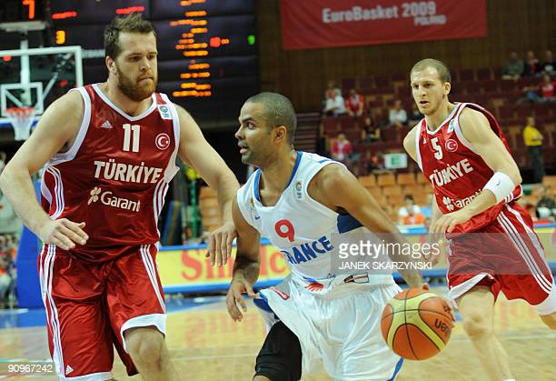 France's Tony Parker dribbles past Turkey's Oguz Savas and Sinan Güler during their 2009 European Championship Basketball play off game for...