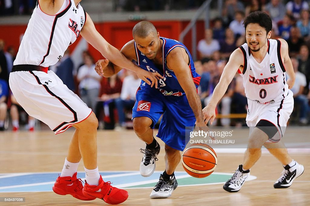 France's Tony Parker (C) vies for the ball with Japan's Joji Takeuchi (L) and Yuta Tabuse (R) during the basketball match between France and Japan at the Kindarena hall in Rouen on June 28, 2016. / AFP / CHARLY