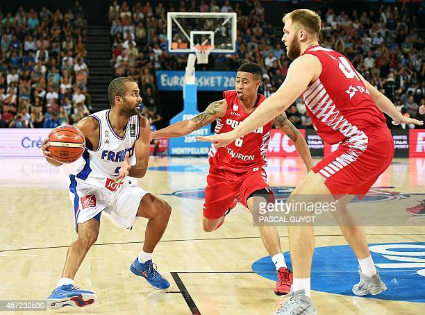 France's Tony Parker vies with Poland's AJ Slaughter and Poland's Przemyslaw Karnowski during the group A qualification basketball match between...