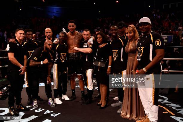France's Tony Yoka poses with his team after defeating USA's Jonathan Rice in their heavyweight bout at the Zenith in Paris on October 14 2017 / AFP...