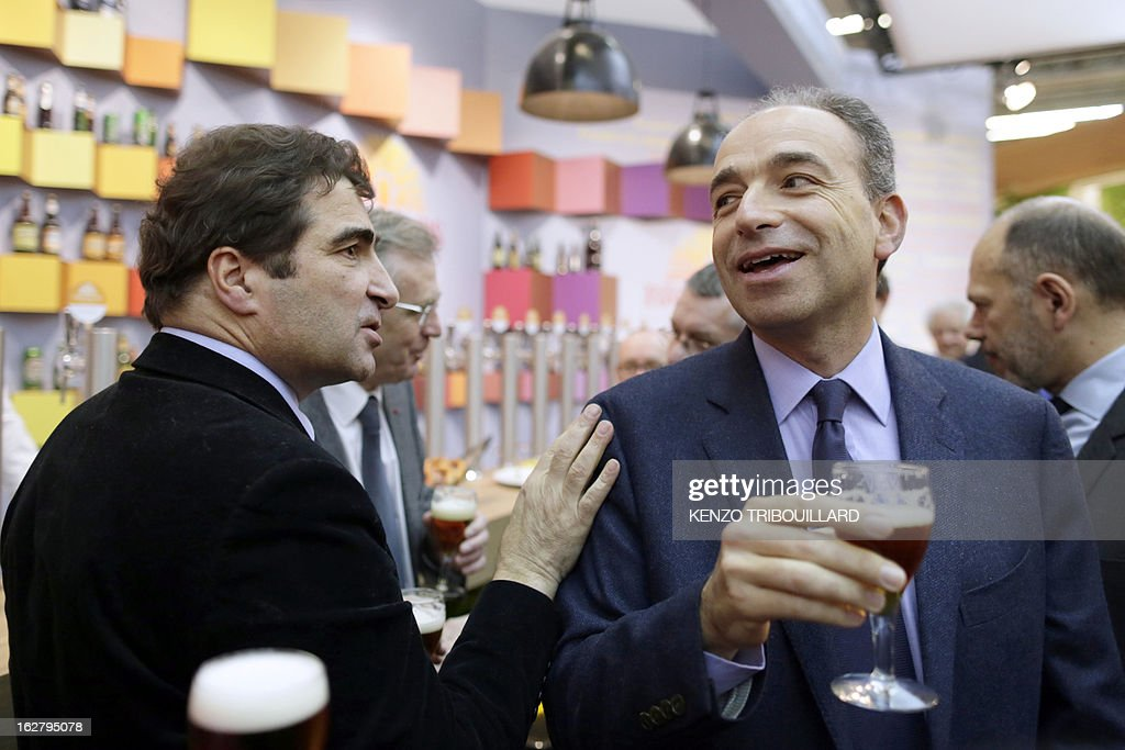France's UMP right-wing opposition party leader Jean-Francois Cope (R) drinks a beer with UMP group at the National Assembly, Christian Jacob, as they visit the International Agriculture Fair of Paris at the Porte de Versailles exhibition center, on February 27, 2013. Some 1,300 exhibitors and 4,000 animals attend the fair which runs from from February 23 to March 3, 2013.