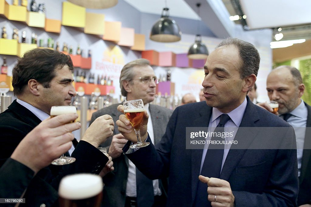 France's UMP right-wing opposition party leader Jean-Francois Cope (R) drinks a beer with UMP group at the National Assembly, Christian Jacob, as they visit the International Agriculture Fair of Paris at the Porte de Versailles exhibition center, on February 27, 2013. Some 1,300 exhibitors and 4,000 animals attend the fair which runs from from February 23 to March 3, 2013. AFP PHOTO KENZO TRIBOUILLARD