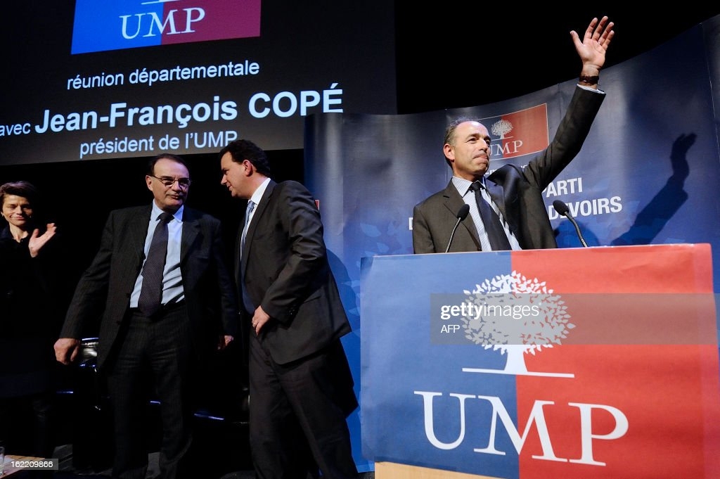 France's UMP right-wing opposition party leader Jean-Francois Cope (R) waves during a political meeting in Rennes, on February 20, 2013.