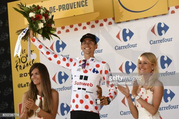 France's Warren Barguil celebrates his polka dot jersey of best climber on the podium at the end of the 2225 km nineteenth stage of the 104th edition...