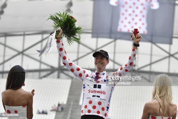 France's Warren Barguil celebrates his polka dot jersey of best climber on the podium at the end of a 225 km individual timetrial the twentieth stage...