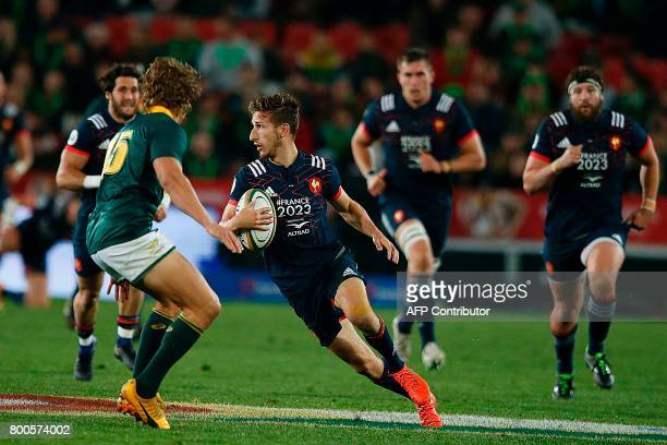 France's wing Vincent Rattez runs with the ball as South Africa's fullback Andries Coetzee looks on during the third rugby union Test match between...