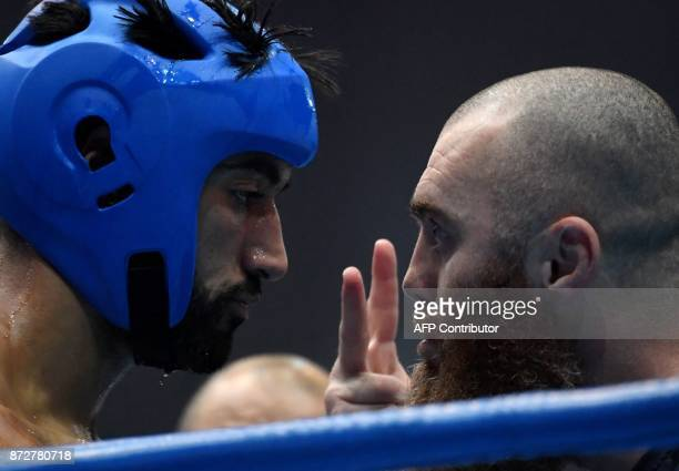 France's Zakaria Laaouatni listens to his coach in the breaktime during his fight with Belarus' Kiryl Marchanka in the K1 75kg category in the ring...