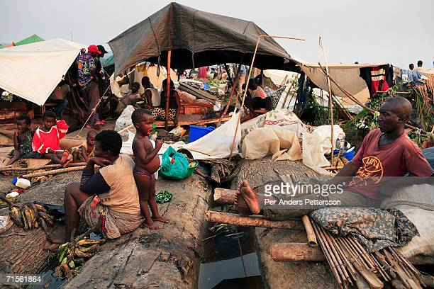Francesca Mboyo prepares to cook for her six children while traveling on a boat made of big trees on the Congo River on July 1 2006 outside Mbandaka...