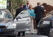Francesca Pascale the girlfriend of former Italian prime minister Silvio Berlusconi plays with a dog as she leaves Palazzo Grazioli on July 31 2013...