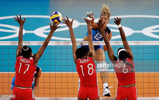 Francesca Piccinini of Italy spikes the ball through the blocks of the Cuban front line during her team's 23 loss to Cuba in the women's indoor...