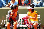 Francesca Schiavone of Italy talks to Kimiko DateKrumm of Japan during a break in play in their Women's Doubles match against Petra Cetkovska of...